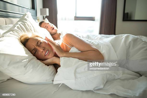 Man snoring, woman frustrated-Couple in bed