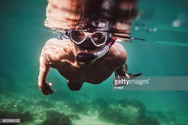 Man snorkeling underwater in sea with mask