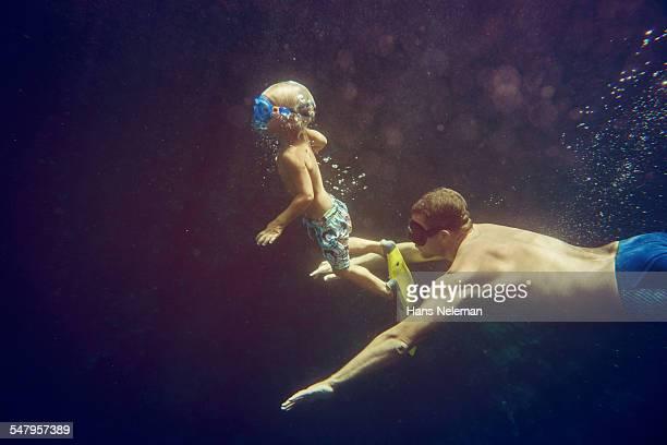 Man snorkeling with boy in the sea, underwater vie