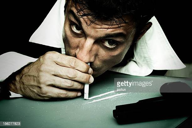 man snorting cocaine off table - cocaine stock photos and pictures