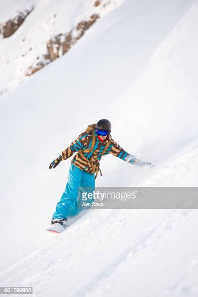 Man snowboarding downhill seep slope