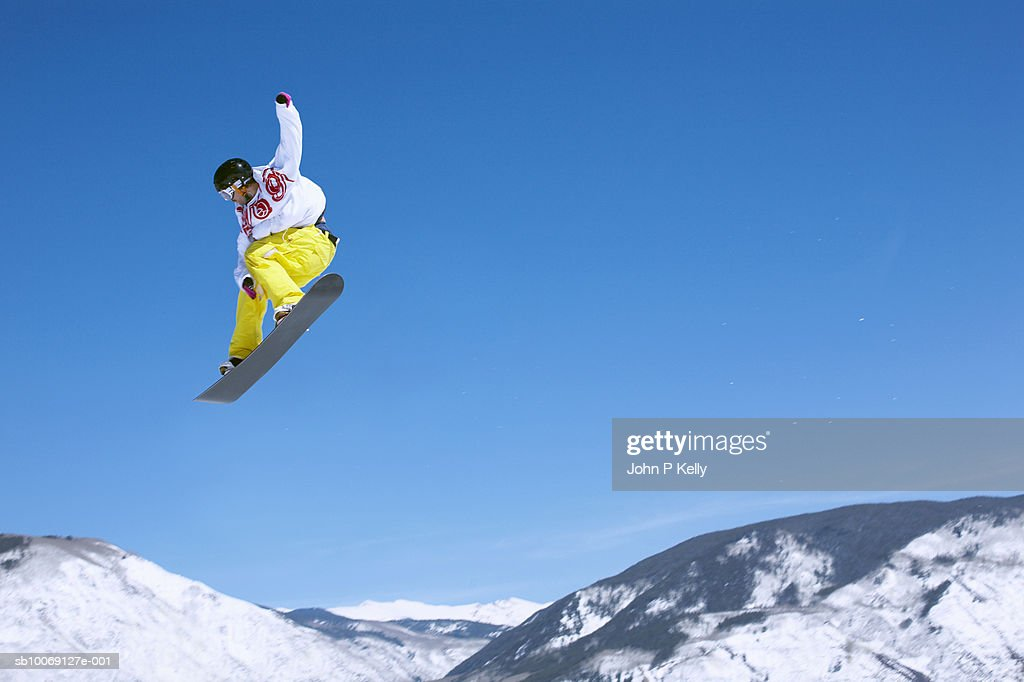 Man snowboarding, jumping in mid-air, low angle view : Stockfoto