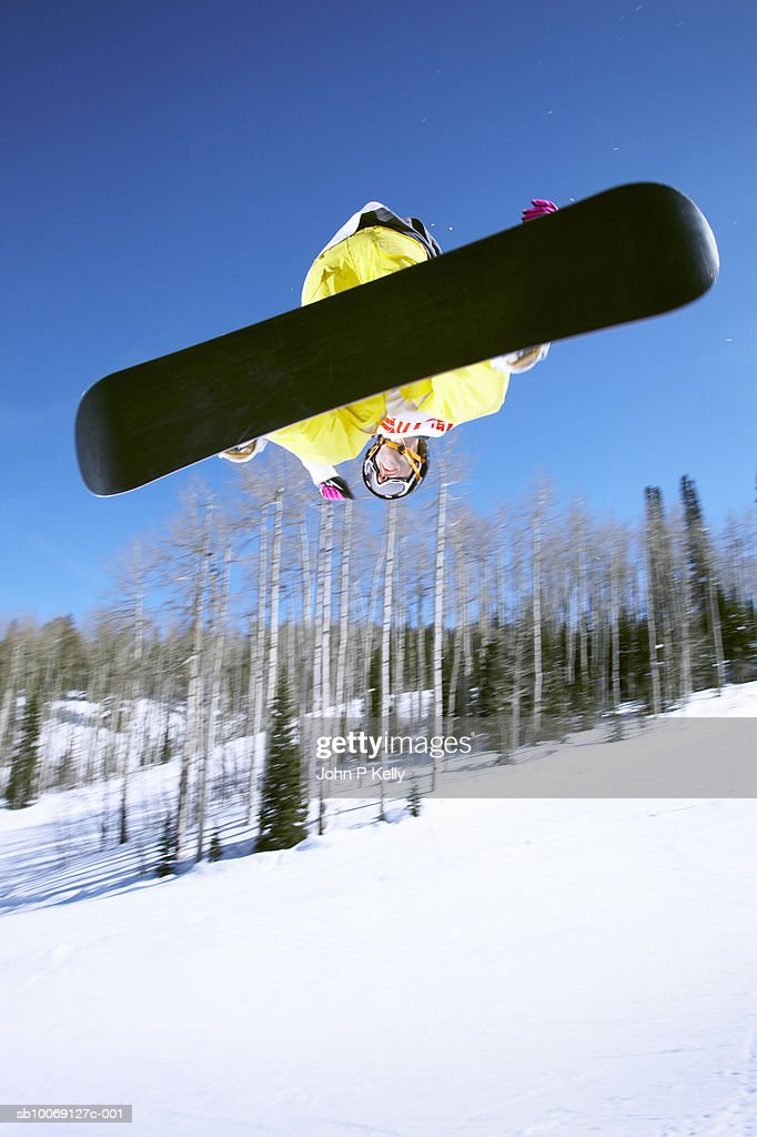 Man snowboarding, jumping in mid-air, upward view : Stockfoto