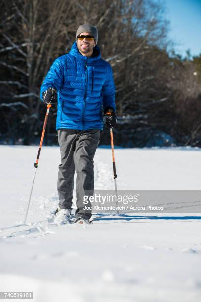 Man snowshoeing on sunny winter day