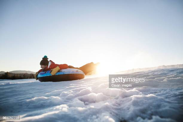 Man snowtubing on mountain against clear sky during sunny day