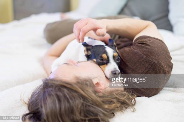 Man snuggling with adorable dog on bed in the morning