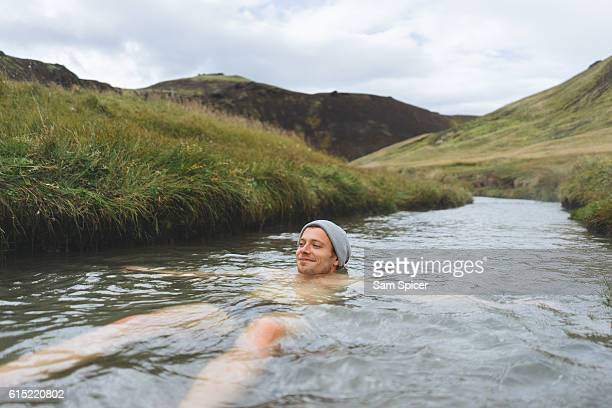 Man soaking in natural hot spring surrounded by nature in Iceland