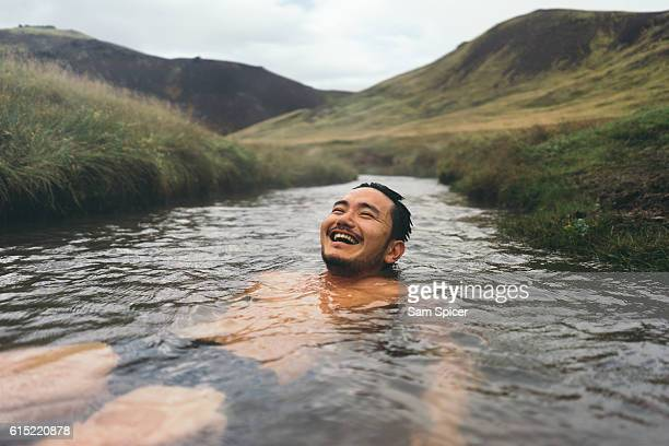 man soaking in natural hot spring surrounded by nature in iceland - hot spring stock pictures, royalty-free photos & images