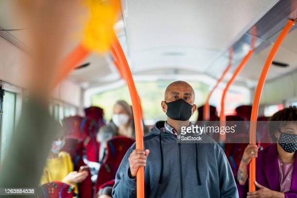 man social distancing on a bus - bus stock pictures, royalty-free photos & images