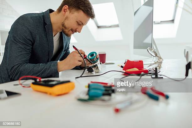 Man Soldering a circuit board in his office.