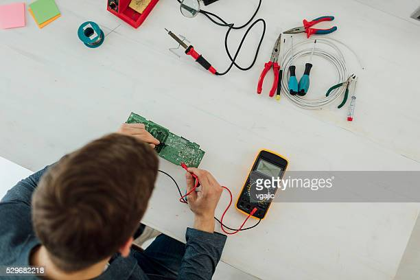 Man Soldering a circuit board in his tech office.