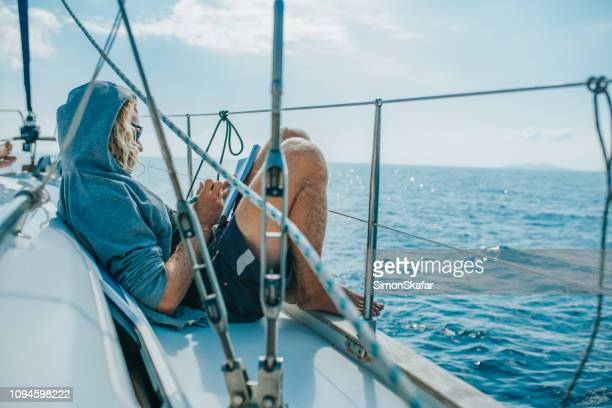 Man solving crossword puzzle on sailing boat