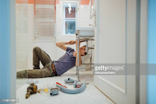 man solving plumbing problems in his bathroom - adjusting stock pictures, royalty-free photos & images