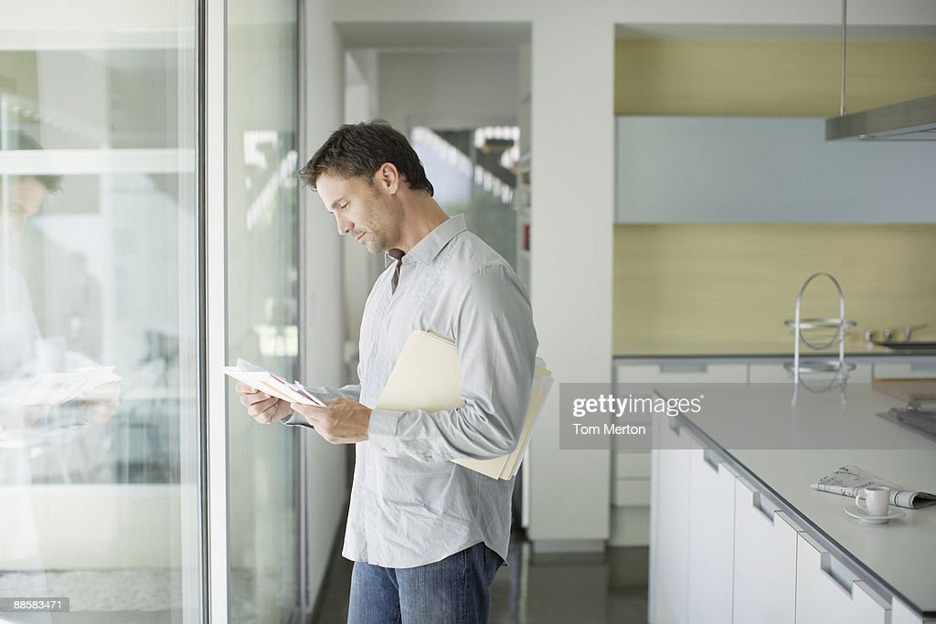 Man sorting mail at home : Stock Photo