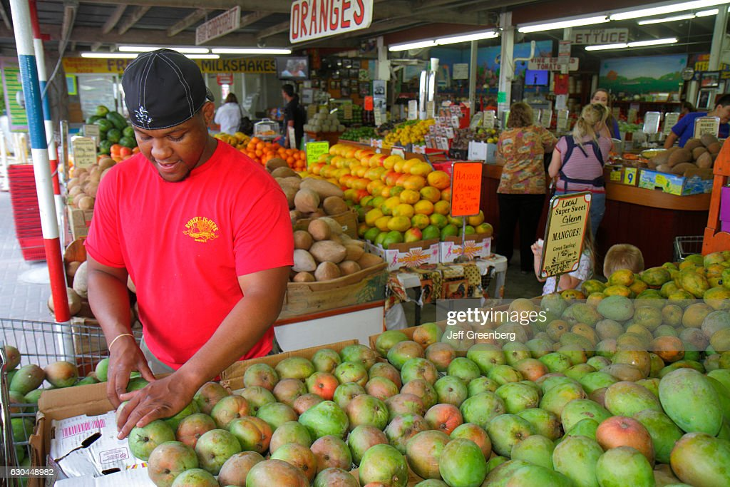 A man sorting out mangoes at the Robert Is Here market. : News Photo