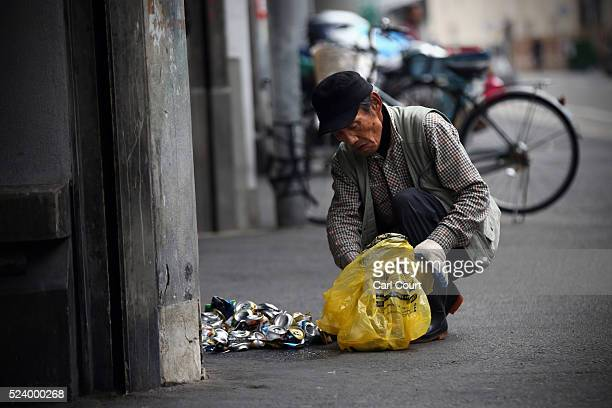 A man sorts cans in the slum area of Kamagasaki on April 24 2016 in Osaka Japan Kamagasaki a district in Japan's second largest city Osaka is home to...