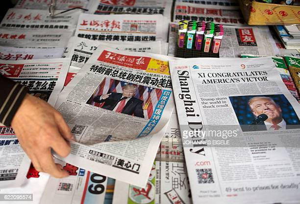A man sorts Chinese newspapers featuring Donald Trump's victory in the US presidential elections on their front pages in Shanghai on November 10 2016...