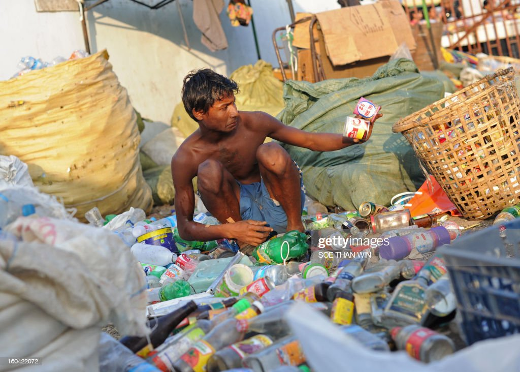 A man sorts containers and used bottles he collected for recycling near a pier in Yangon on January 31, 2013. AFP PHOTO/Soe Than WIN