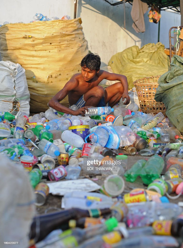 A man sorts used bottles he collected for recycling near a pier in Yangon on January 31, 2013. AFP PHOTO/Soe Than WIN