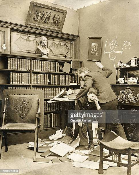 A man spanks a boy for making a mess in his study
