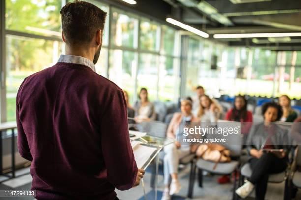 hombre hablando delante de la audiencia - grupo mediano de personas fotografías e imágenes de stock