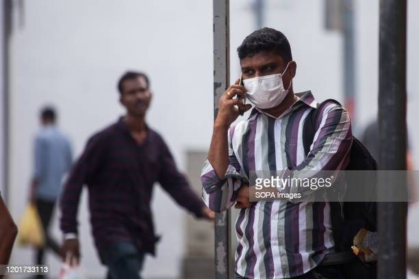 A man speaking on phone while wearing a protective face mask in the ethnic district of Little India following the corona virus threat Singapore...