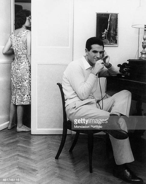 Man speaking over the phone. His wife eavesdropping behind the door. 1959