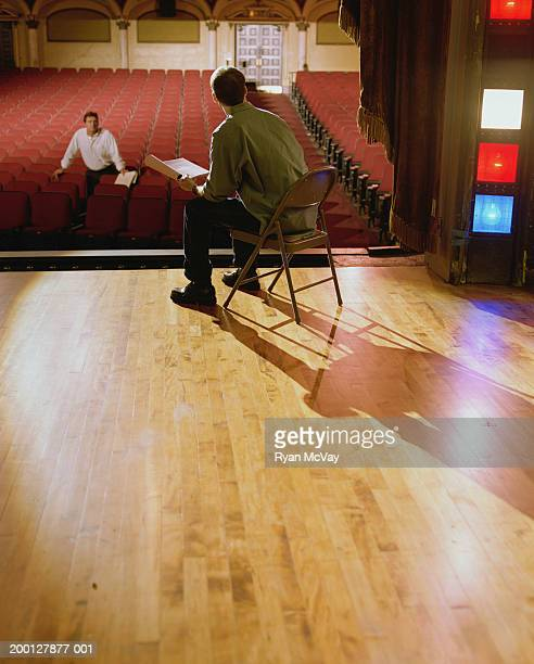 Man speaking to actor sitting on stage