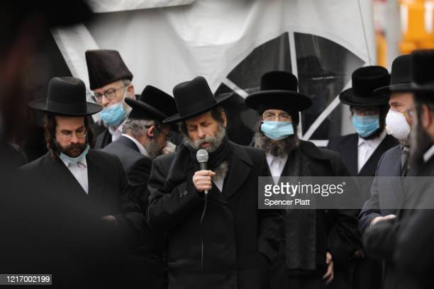 Man speaks as hundreds of members of the Orthodox Jewish community wearing face masks attend the funeral for a rabbi who died from the coronavirus in...