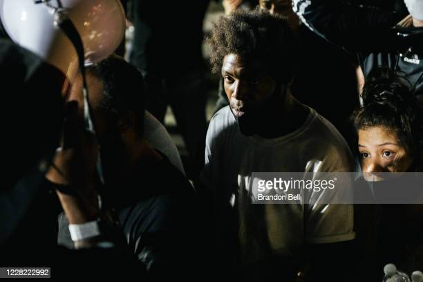 Man speaks at a site where a demonstrator was killed on August 26, 2020 in Kenosha, Wisconsin. On August 25, 17-year-old Kyle Rittenhouse shot and...