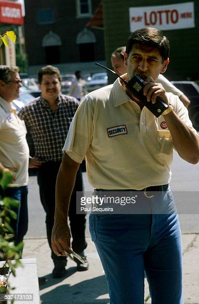 A man speaks into a walkie talkie while patrolling the streets near Wrigley Field against scalpers selling Chicago Cubs tickets Chicago Illinois 1984