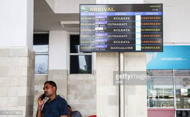 A man speaks on a mobile phone as a flight information board displays cancelled flights following Cyclone Fani at Maharaja Bir Bikram Airport on the...