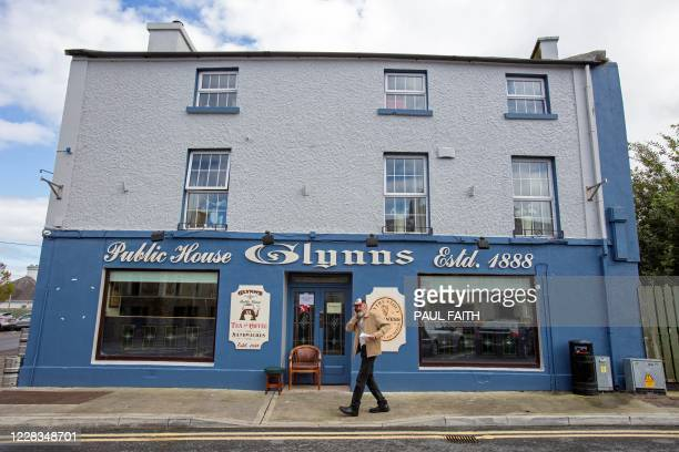 Man speaks on a mobile phone as he passes Glynn's bar, the only open pub in the rural village of Dunmore, west of Ireland, on September 3, 2020. - In...