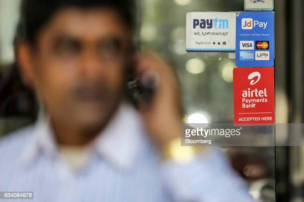 A man speaks on a mobile phone as signage for digital payment services Paytm operated by One97 Communications Ltd top left JD Pay operated by Just...