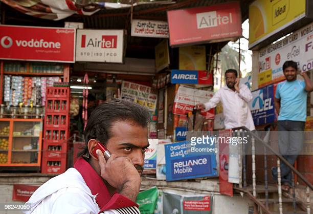 A man speaks on a mobile phone in front of a shop selling prepaid recharges for different mobile providers in Bangalore India on Thursday Jan 28 2010...
