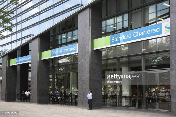 A man speaks on a mobile phone outside a Standard Chartered Plc bank branch in the central business district of Singapore on Monday Feb 12 2018...