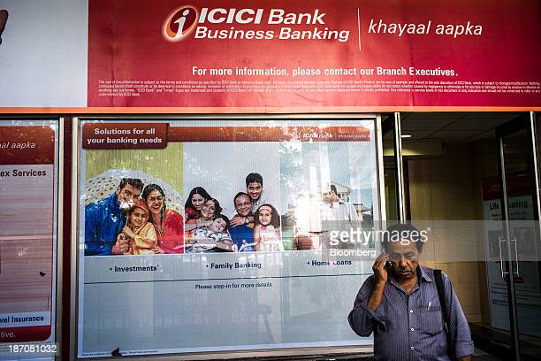 A man speaks on a mobile phone outside an ICICI Bank Ltd branch in Kolkata West Bengal India on Thursday Oct 31 2013 Indian stocks fell for the first...