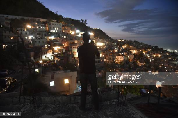 Man speaks on his cell phone facing the neighborhood of Jalousie, in the commune of Petion Ville, Port-au-Prince, on December 16, 2018. - Jalousie is...