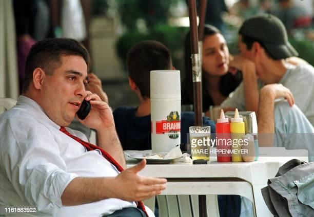 Man speaks on his cellular phone while sitting outside with his beer 2 July 1999. Un paulista habla por celular mientras toma cerveza en una terraza...