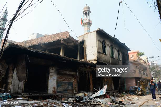 Man speaks on his mobile phone as he walks past a burnt-out mosque and shops following clashes between people supporting and opposing a contentious...