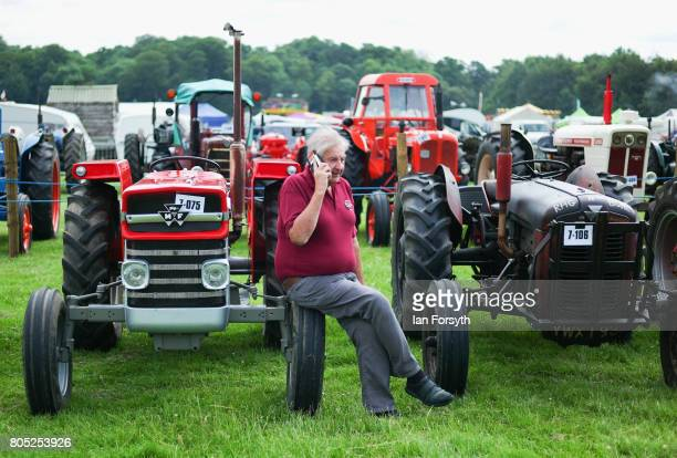 A man speaks on his phone as he sits on the wheel of a vintage tractor during the Duncombe Park Steam Rally on July 1 2017 in Helmsley United Kingdom...