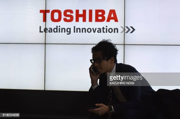A man speaks on his phone in front of the logo of Japan's Toshiba Corp at the company's headquarters in Tokyo on February 14 2018 Troubled Japanese...
