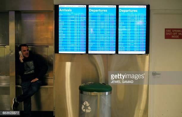 A man speaks on his phone next to screens displaying flight status at LaGuardia airport in New York on March 15 2017 Winter Storm Stella lashed the...