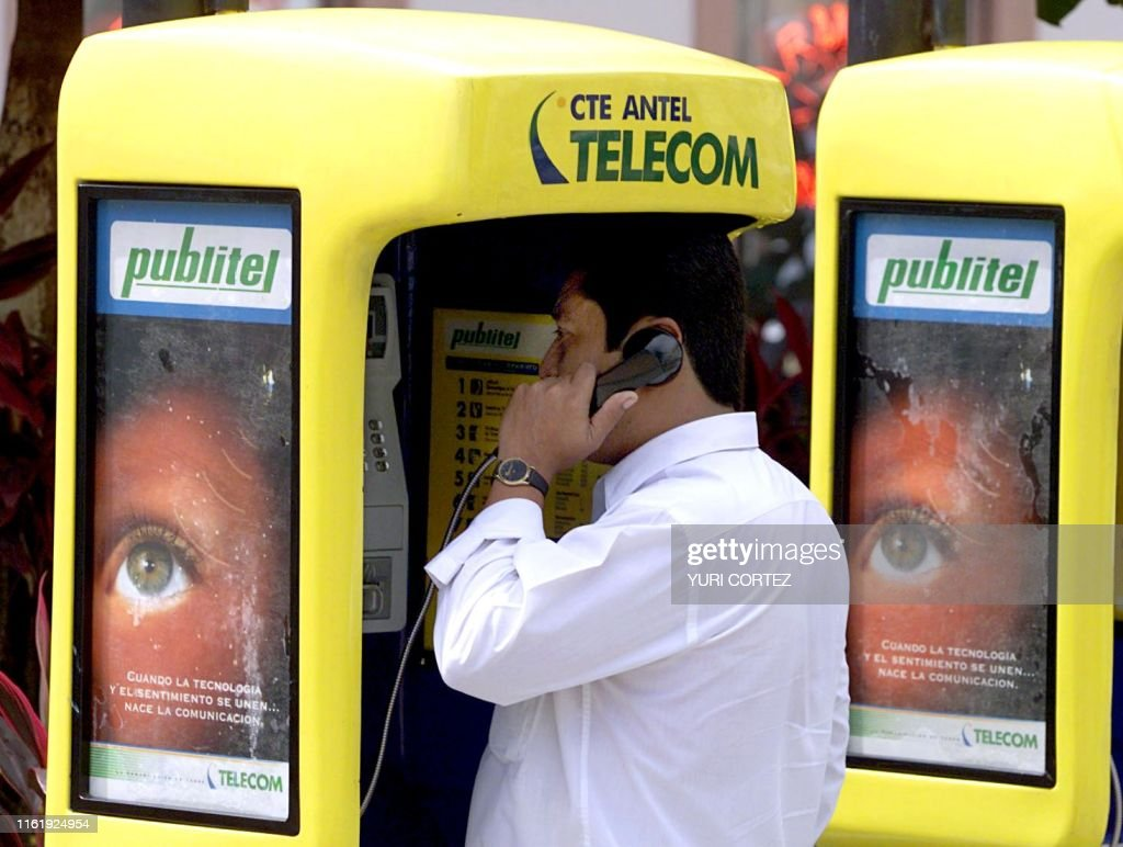 A man speaks on the telephone 08 June 2000 in a phone box of