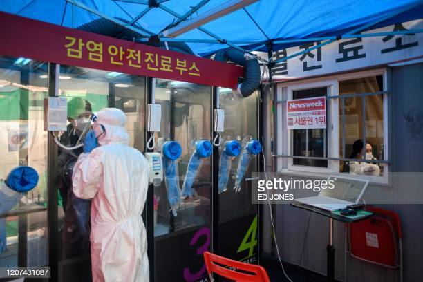 Man speaks to a nurse during a COVID-19 novel coronavirus test at a testing booth outside Yangji hospital in Seoul on March 17, 2020. - A South...