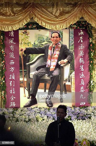 A man speaks while standing in front of a portrait of Taiwanese gang boss Hsu Hai Ching during his funeral in Taipei 29 May 2005 Thousands of gang...