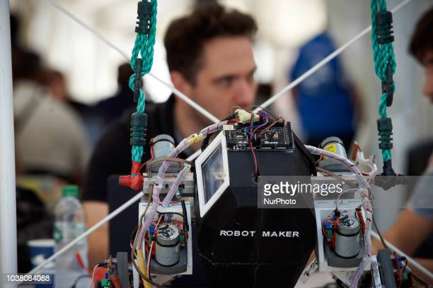 A man speaks with another about his new creation Robot MakerA robots race took place in Toulouse Machines are either cars or walking robots They were...