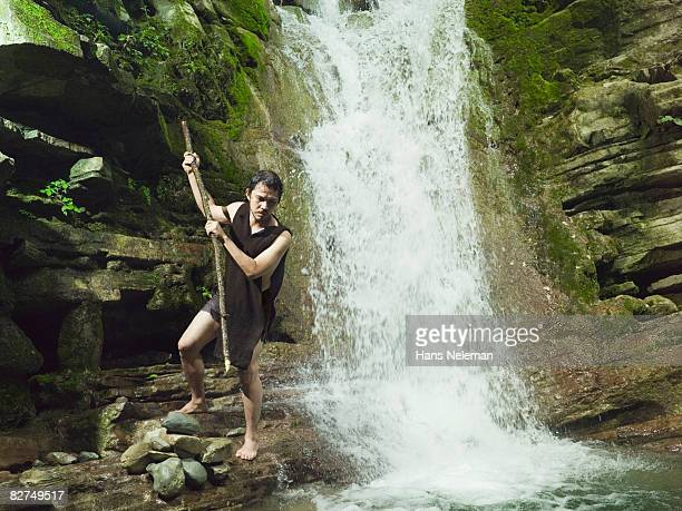 Man spearing fish in a waterfall