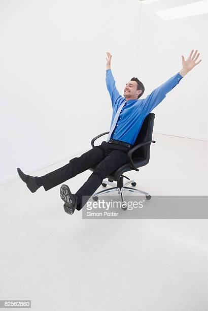 man speeds through office on chair - office chair stock pictures, royalty-free photos & images