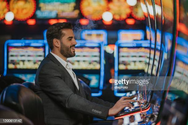 man spending time at casino - gambling table stock pictures, royalty-free photos & images